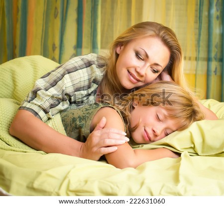 Beautiful happy smiling mother embracing her cute daughter sleeping in bed. - stock photo