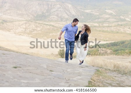 Beautiful happy smiling running couple in love outdoors - stock photo