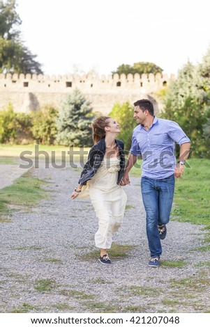 Beautiful happy smiling running couple outdoors - stock photo
