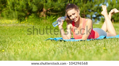 Beautiful happy smiling sport fitness model outside on summer / spring day.