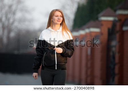 Beautiful happy smiling sporty girl in sportswear walking in earphones during sport workout in the morning street, healthy active lifestyle concept - stock photo