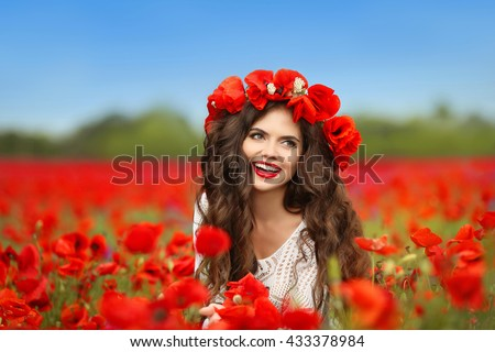Beautiful happy smiling teen girl portrait with red flowers on head enjoying in poppies field nature background.  - stock photo