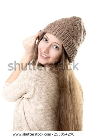 Beautiful happy smiling teenage girl in casual clothes trying on beige knitted hat, isolated - stock photo