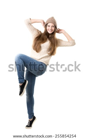 Beautiful happy smiling teenage girl wearing jeans, jersey and knitted hat jumping with delight, dancing, isolated - stock photo