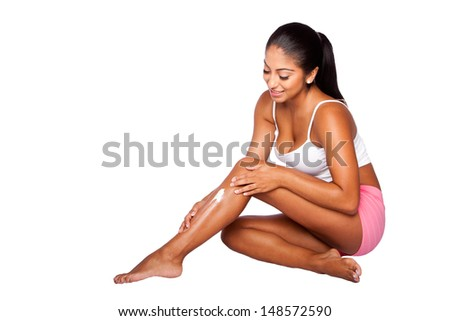 Beautiful happy smiling woman applying exfoliating moisturizing lotion cream on leg, bodycare skincare concept. - stock photo