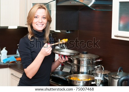 Beautiful happy smiling woman in kitchen interior cooking