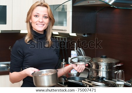 Beautiful happy smiling woman in kitchen interior holding a pan