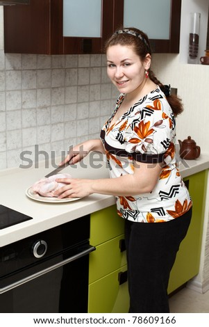 Beautiful happy smiling woman in kitchen interior with chicken - stock photo