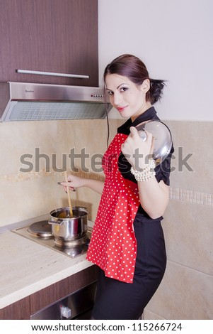 Beautiful happy smiling woman in the kitchen interior cooking - stock photo