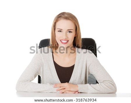 Beautiful happy, smiling woman sitting by a desk. Isolated on white.