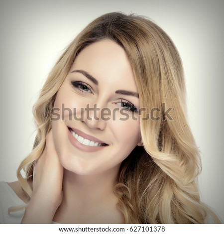 Beautiful happy smiling young blonde woman. Added toning and vignetting.