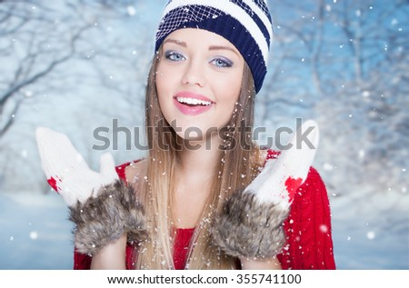 Beautiful happy smiling young surprised woman wearing winter gloves covered with snow flakes. Christmas portrait concept. Winter landscape background - stock photo