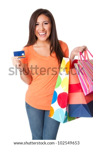 Beautiful Happy smiling young woman on shopping spree with credit card lastic money carrying colorful bags with merchandise presents, isolated.