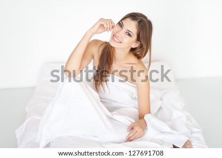 Beautiful happy smiling young woman sitting on bed
