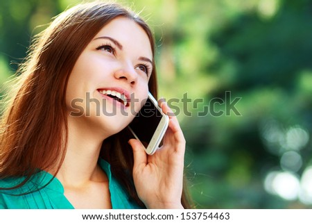 beautiful happy smiling young woman using mobile, sitting in park, smiling