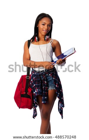 Beautiful happy student standing with binders and bag, on white.