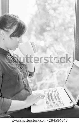 Beautiful happy student with a laptop sitting against a bright window and drinking coffee or tea. Young woman learn and using a computer connected to the network via wifi, 4g - stock photo