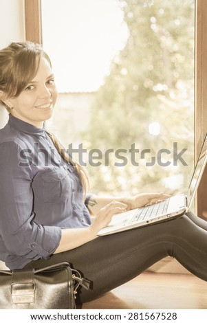 Beautiful happy student with a laptop sitting against a bright window. Young woman learn and using a computer connected to the network via wifi, 4g - stock photo