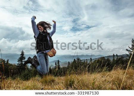 beautiful happy stylish traveling girl jumping  in the mountains on a background of a forest - stock photo