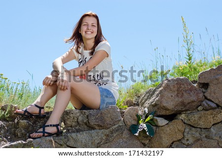 Beautiful happy teenage girl sitting on blue sky background and smiling