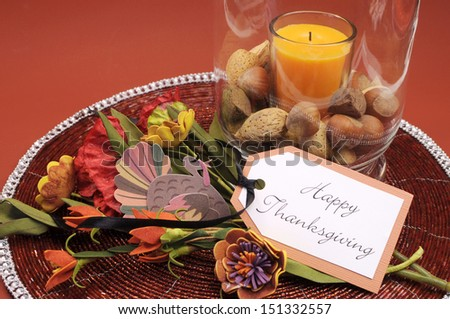 Beautiful Happy Thanksgiving table setting centerpiece with orange candle and nuts in decorative glass hurricane lamp vase and autumn arrangement Vertical with turkey decoration.