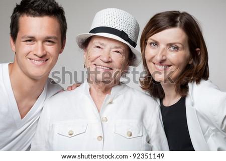 Beautiful happy three generations family posing on gray background. - stock photo