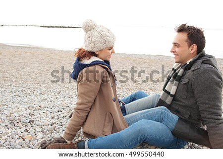 Beautiful happy tourist couple sitting on pebble beach winter holiday, talking in romantic travel lifestyle outdoors. Boyfriend and girlfriend close relationship, first love, nature destination.