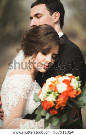 Beautiful happy wedding couple walking in the park on their day with bouquet