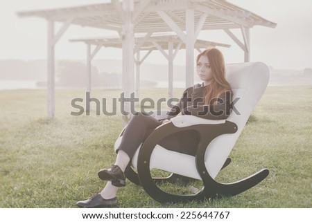 beautiful happy woman has a rest in chair on bank of the lake morning