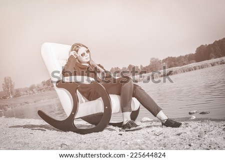 beautiful happy woman has a rest in chair on bank of the lake morning - stock photo