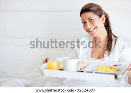 Beautiful happy woman having breakfast in bed - stock photo
