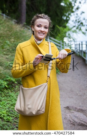 Beautiful happy woman holding smartphone on selfie stick and looking at camera