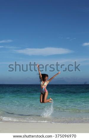 Beautiful happy woman in bikni jump on tropical beach - stock photo