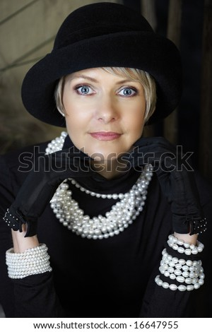 beautiful happy woman in her mid 40s with blond short hair wearing fresh water pearls, hat and gloves