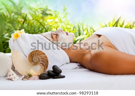 Beautiful happy woman in the spa making face mask treatment - stock photo