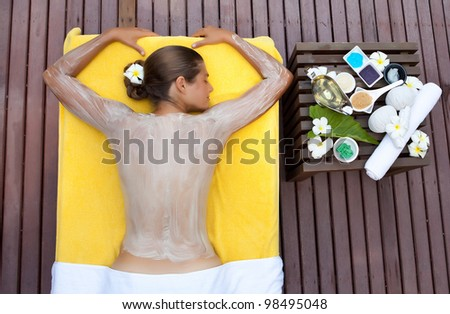 Beautiful happy woman in tropical spa making face mask treatment - stock photo