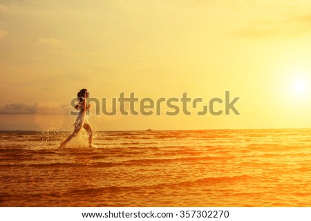 Beautiful happy woman in white dress running on the sea on sunset, freedom and travel abstract concept