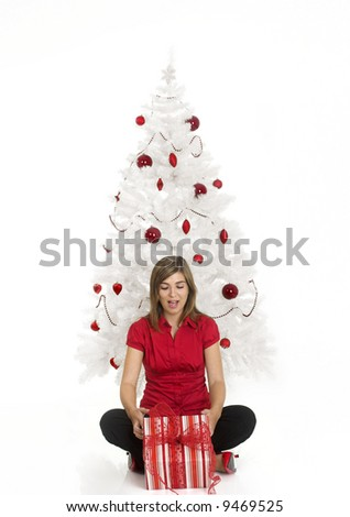 Beautiful happy woman near a white Christmas tree holding Christmas presents