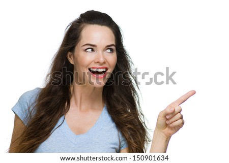 Beautiful happy woman pointing and looking at copyspace. Isolated on white. - stock photo
