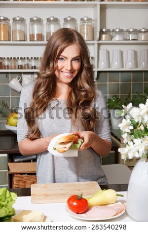 Beautiful happy woman preparing sandwich - stock photo