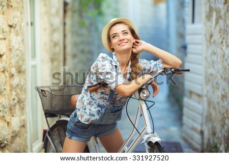 Beautiful happy woman with bicycle on street of old town - stock photo