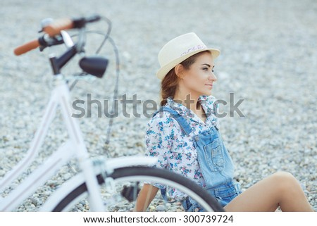 Beautiful happy woman with bicycle on the beach - stock photo