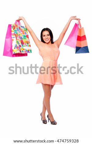 Beautiful happy woman with shopping bags on shoppingspree standing cute with arms in air, consumer lifestyle concept.
