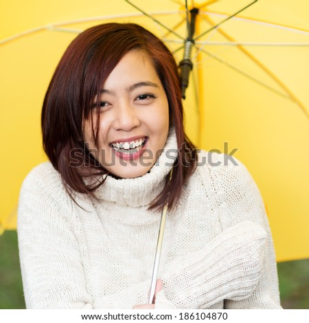 Beautiful happy young Asian woman sheltering under a yellow umbrella in a warm polo neck sweater standing laughing at the camera - stock photo