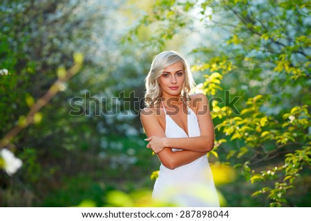 Beautiful happy young blonde woman enjoying smell in a flowering spring garden during sunset - stock photo