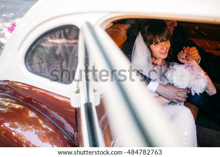 Beautiful happy young bride and groom kissing in retro auto. Embracing near old limousine. Brown color car.