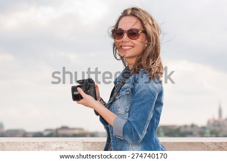 Beautiful happy young brunette taking photographs. - stock photo