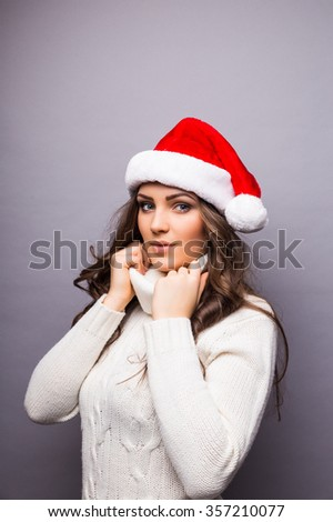 Beautiful happy young Caucasian brunette woman wearing Santa Claus beanie hat  and white sweater. Christmas concepts. Isolated on white.