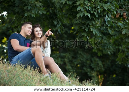 Beautiful happy young couple in love wearing casual clothes relaxing under maple tree in park, sitting together on grass on summer day, guy pointing his finger into the distance, copyspace