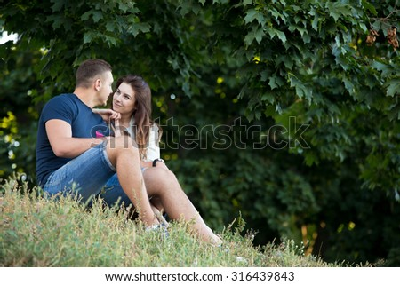 Beautiful happy young couple in love wearing casual clothes resting under maple trees in park, looking at each other, sitting, snuggling together on grass on summer day, copy space